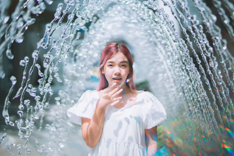Portrait of young woman standing in water