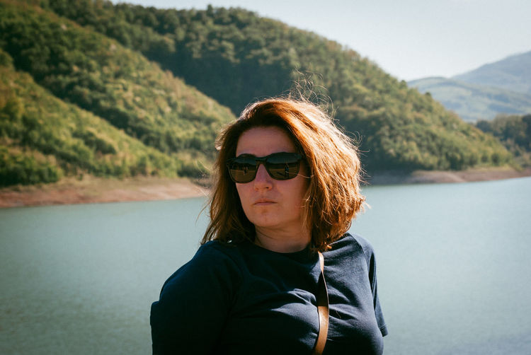 Portrait of young woman wearing sunglasses against lake