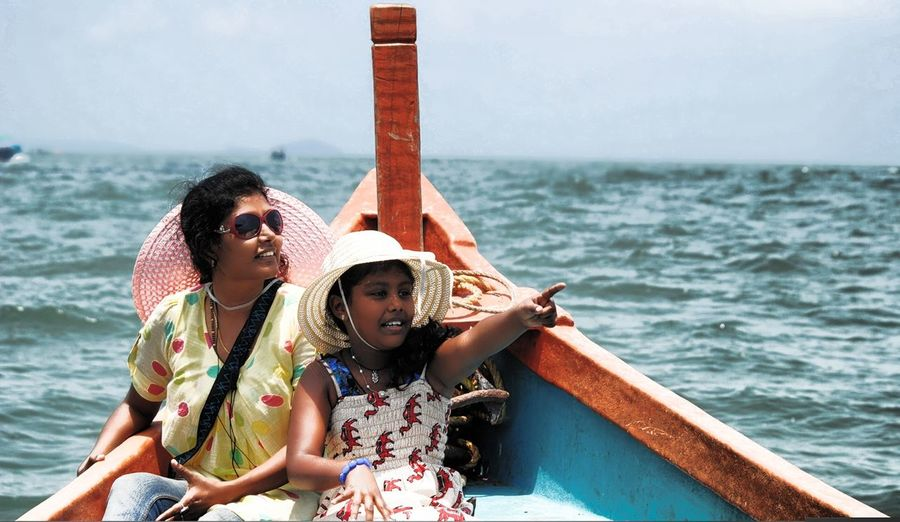 Daughter with mother pointing in boat on sea