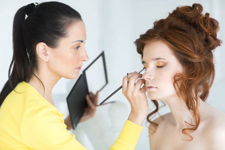 Female artist applying make-up to bride in studio
