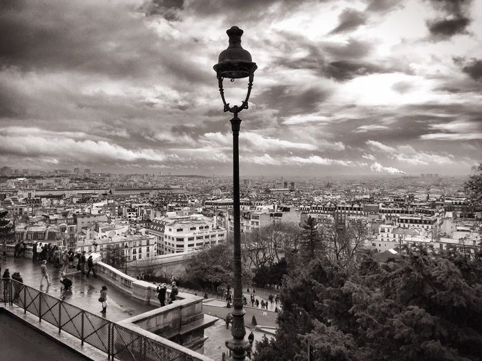 Street lamp by cityscape against sky