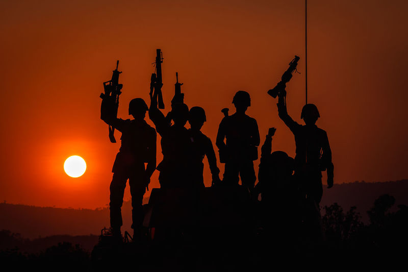 Beauty In Nature Group Group Of People Gun Holding Land Lifestyles Medium Group Of People Men Nature Orange Color Outdoors People Real People Silhouette Sky Soldiers Uniform Standing Sun Sunset Togetherness