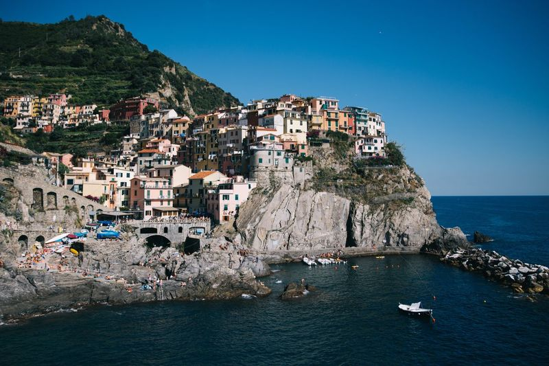 View of cinque terre by sea against clear blue sky
