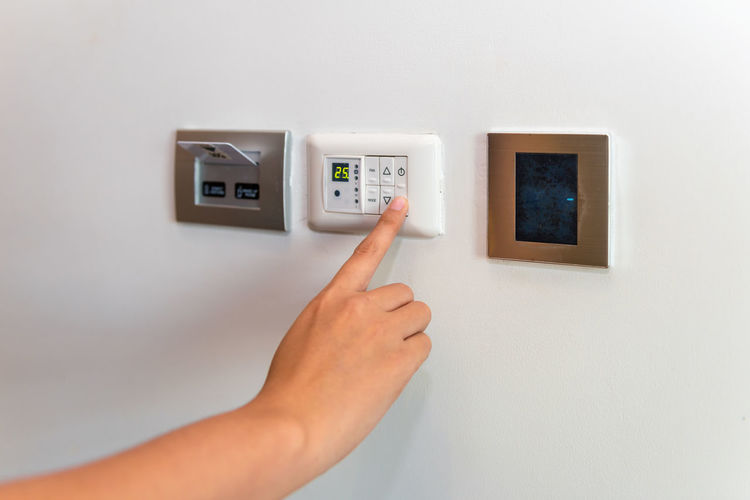 Close-up of human hand using air conditioner remote on white wall at home