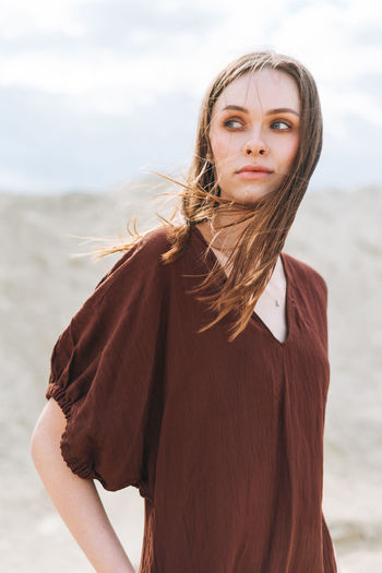 Portrait of beautiful young woman standing on beach