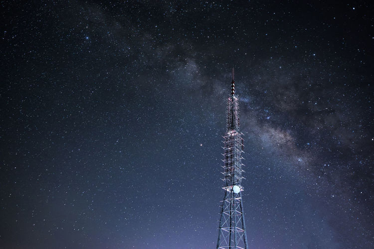 Low angle view of communications tower against galaxy