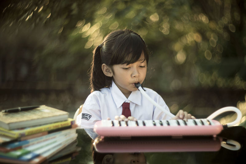 Cute girl playing piano while sitting at desk
