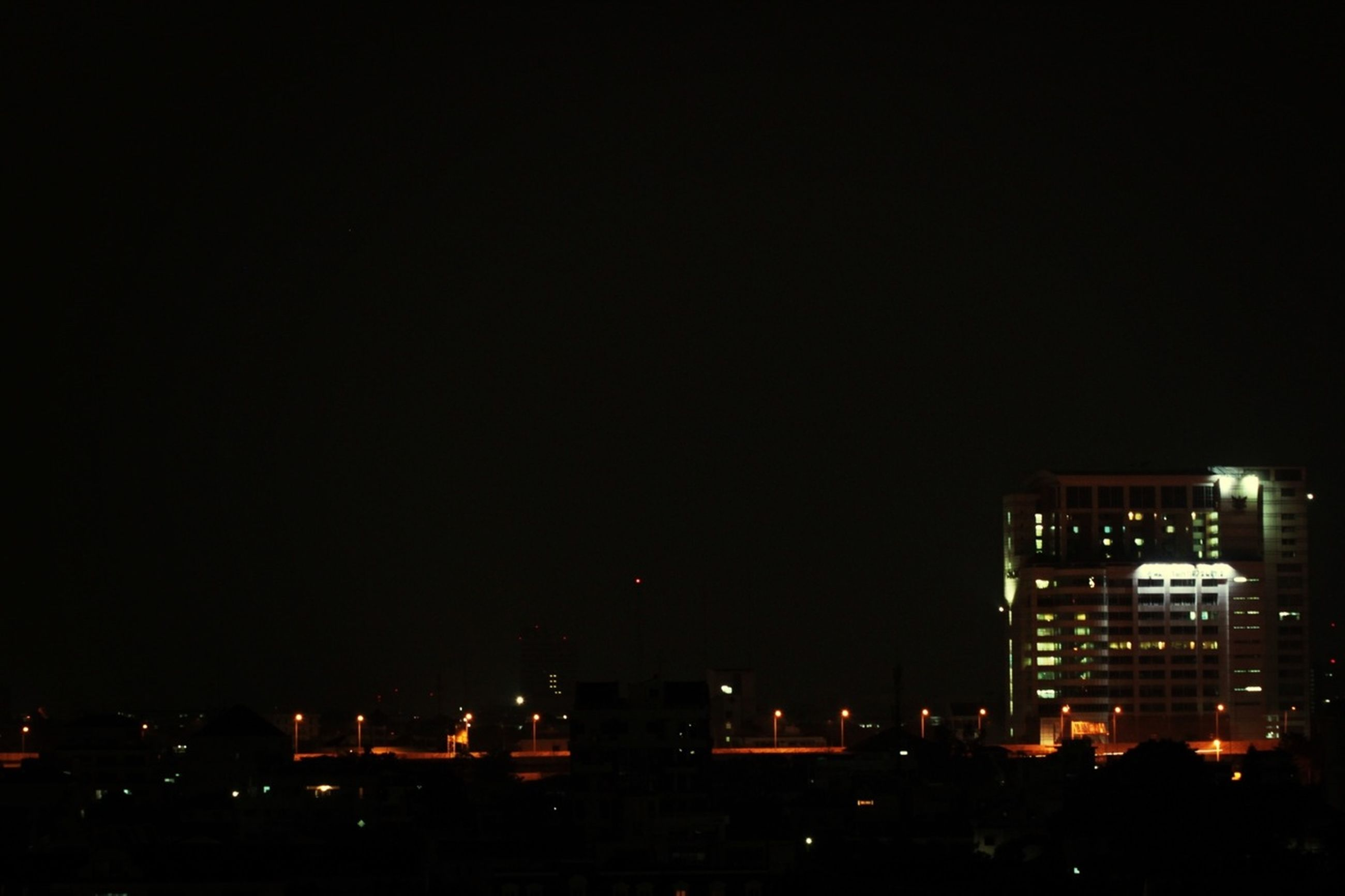 night, building exterior, illuminated, city, architecture, built structure, copy space, cityscape, clear sky, skyscraper, dark, city life, modern, urban skyline, office building, tall - high, tower, residential building, outdoors, building