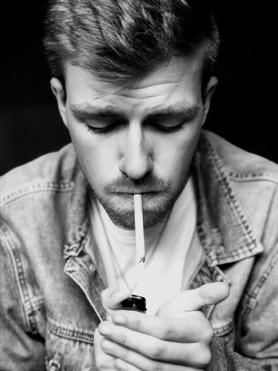 Young Man Smoking Cigarette Against Black Background