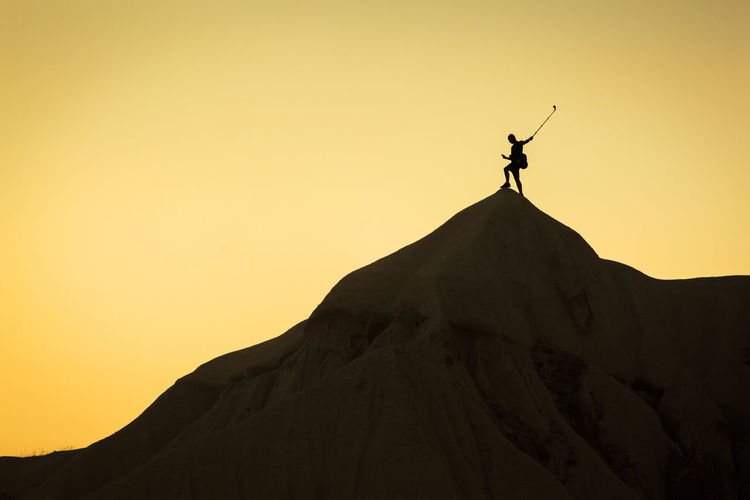 Low angle view of silhouette man standing on mountain against clear sky