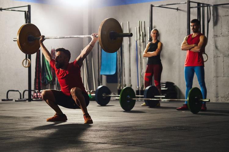Full length of man exercising at gym