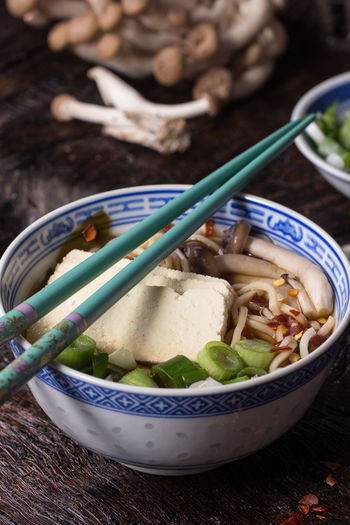 Chinese porcelain bowl of asian ramen soup with feta cheese, noodles, spring onion and mushrooms, served with turquoise chopsticks over old wooden table. Dark rustic style. Asian  Asian Dish Dinner Ingredients Asian Food Chopsticks Dark Photography Egg Mushroom Onion Ramen Ramen Bowl Ramen Noodles Ready-to-eat Rustic Style Soup Table Tofu Wooden