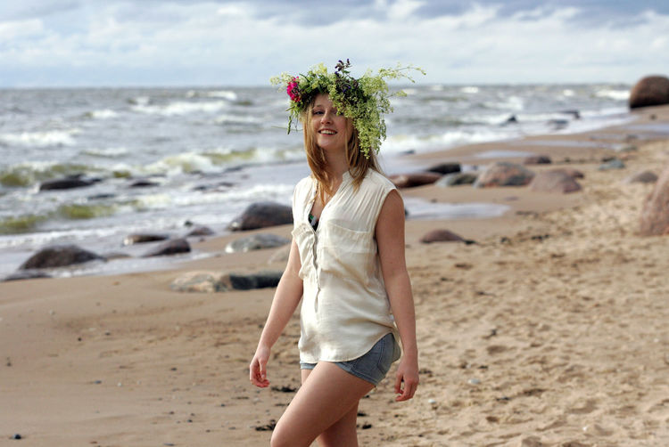 Full length of smiling young woman on beach