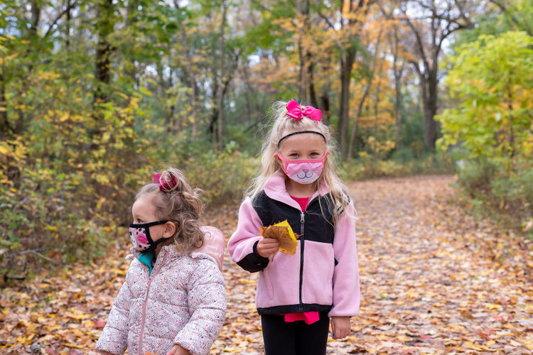 Happy girl smiling while standing on autumn leaves