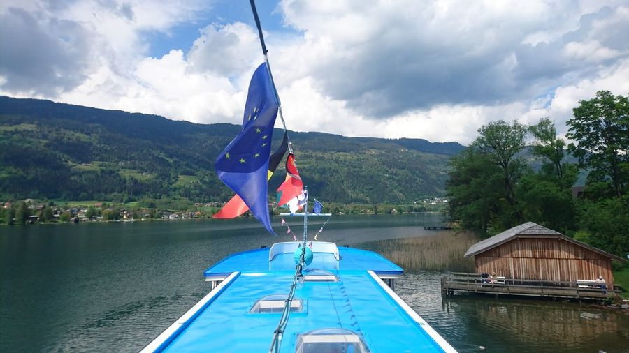 Flags On Boat In Lake Against Cloudy Sky