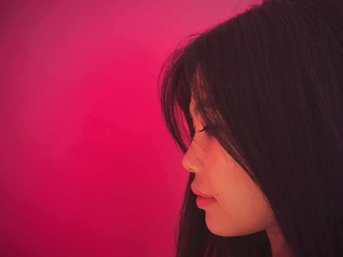 Side view of young woman against pink background