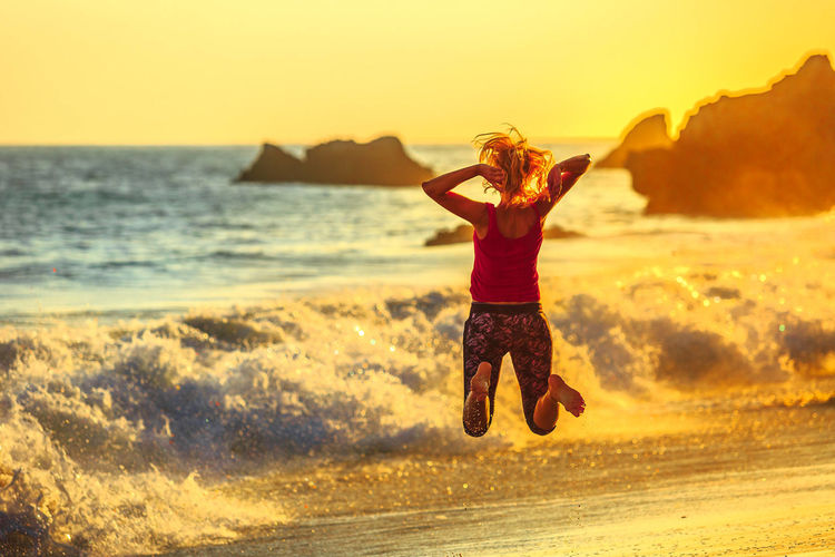 California West Coast carefree. Freedom woman jumping on seashore of El Matador Beach near Malibu, California, United States. Female jumper between limestone formations on Pacific Ocean. Sunset light. California Dreamin California Coast California United States America American Coastline Sea Beach Tourist Attraction  Travel USA Malibu Malibu Beach Malibu Pier El Matador Beach Limestone Rocks Pacific Ocean Holidays Sumemr Sun Paradise Beach Point Dume Woman Model Sunset Sky One Person Water Land Leisure Activity Beauty In Nature Full Length Nature Real People Horizon Horizon Over Water Scenics - Nature Lifestyles Young Adult Human Arm Outdoors Arms Raised