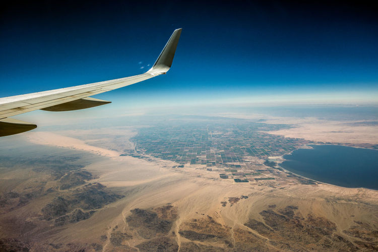Aerial view of airplane flying over landscape against blue sky
