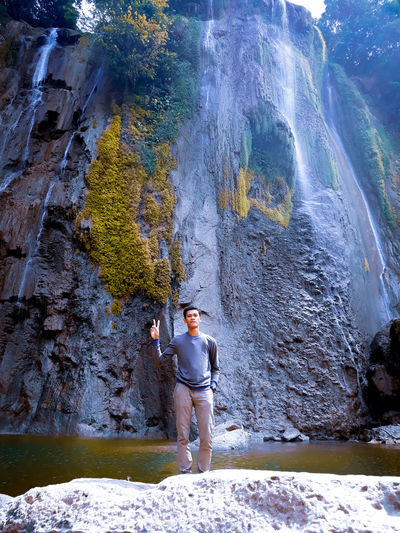 Woman standing on rock against waterfall
