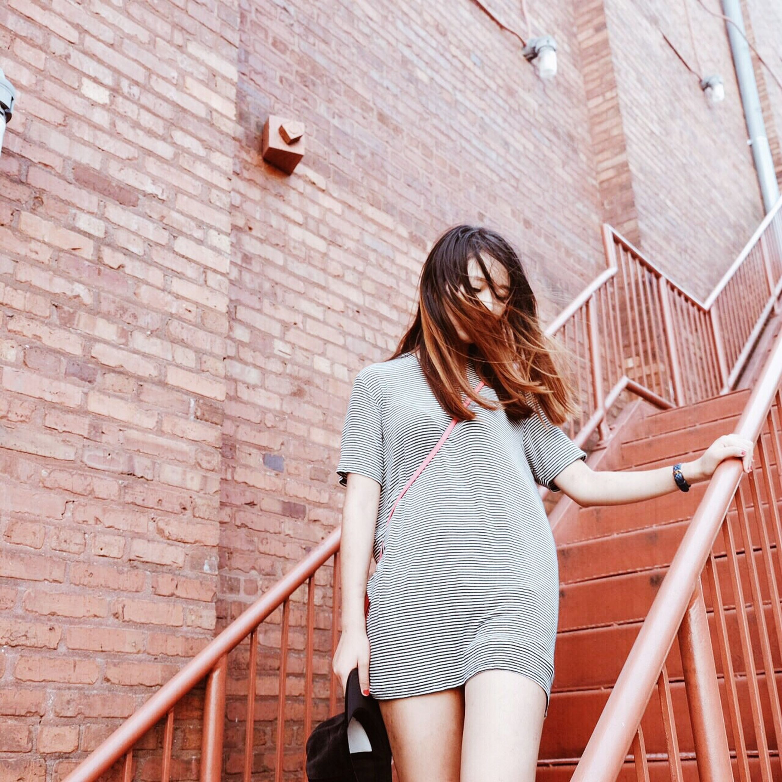 lifestyles, standing, young women, leisure activity, young adult, casual clothing, person, full length, wall - building feature, built structure, architecture, three quarter length, long hair, day, railing, brick wall, outdoors, sitting