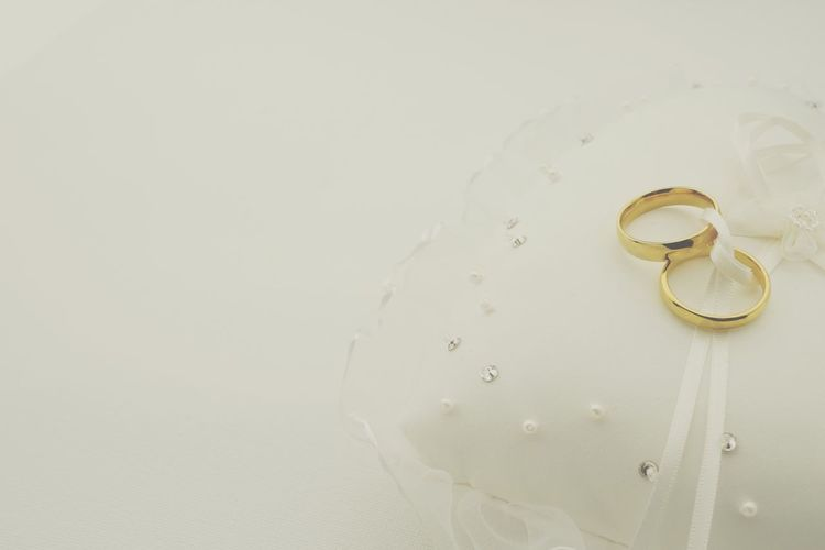 Matte wedding background with rings on ring pillow Beige White Matte Tie The Knot Ring Pillow Jewellery Nobody Wedding Rings Hochzeitseinladung Hochzeit Wedding Invitation Wedding Card Wedding Copy Space Indoors  No People Jewelry Close-up Gold Colored Ring Love Event Life Events Studio Shot
