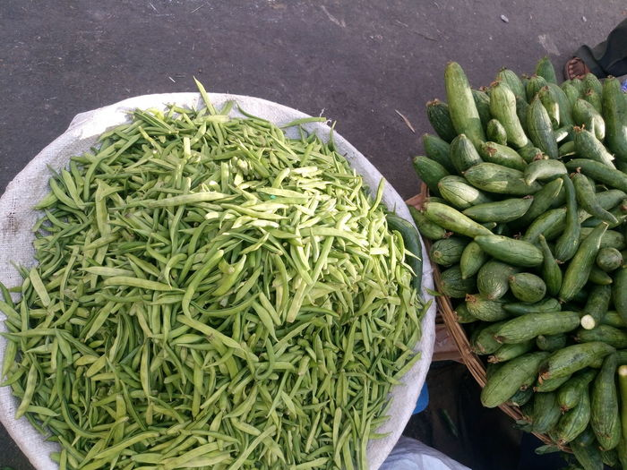 High Angle View Of Sponge Gourds And Green Beans For Sale At Street Market