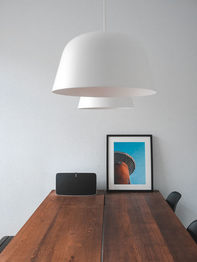 Electric lamp on table against wall at home