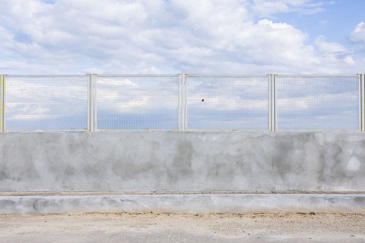 Wall by bridge against sky