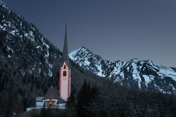 Church by snowcapped mountains against clear sky during winter