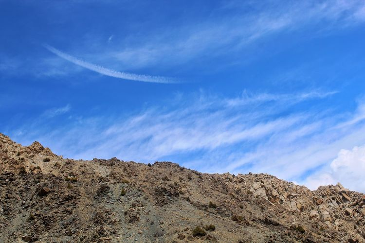 Low angle view of mountain against blue sky