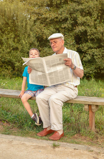 Senior man reading and bored cute child looking over the newspaper sitting on park bench. Two different generations concept. Relaxation Relax Mature Outside Cute Caucasian Age Hat Parent Complicity Together Education Sitting Male Adult Background Smiling Happy Leisure Lifestyle Old People Real Two Elderly Seat Nature Family Learning Teaching Bored Generation Outdoors Grandparent Grandfather Grandchild Grandson Park Bench Looking Reading Paper News Newspaper Boy Kid Child Man Senior