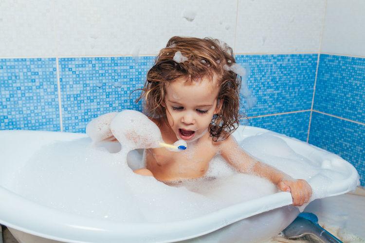 Girl taking bath in bathtub
