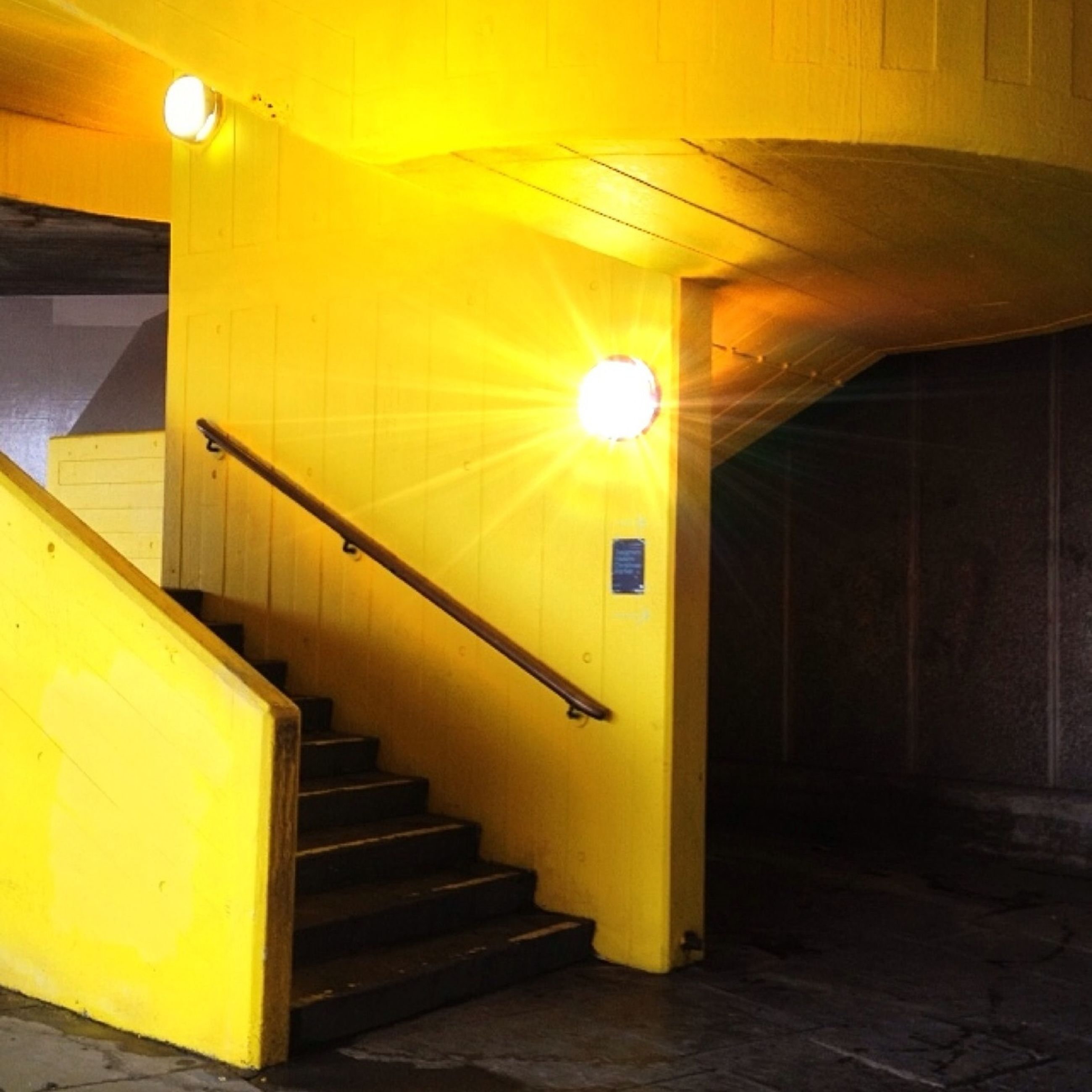 indoors, illuminated, steps and staircases, steps, staircase, yellow, built structure, architecture, lighting equipment, railing, ceiling, wall - building feature, escalator, absence, empty, modern, convenience, subway station, public transportation, no people