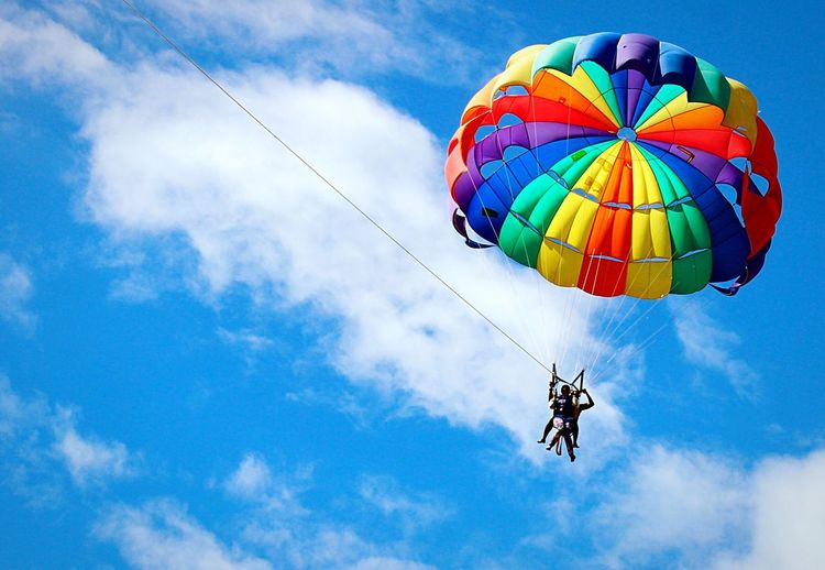 Low angle view of people parasailing against blue sky on sunny day