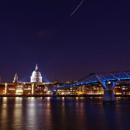 Illuminated london millennium footbridge over river in city at night