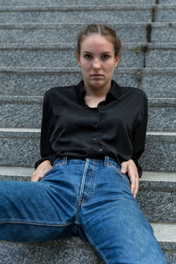 Young woman leaning back on staircase One Person Casual Clothing Jeans Staircase Caucasian Young Woman Young Adult Outdoors Outside Natural Lighting Sitting Looking At Camera Beautiful Woman Front View Portrait Leaning Back Jeans Serious Posing