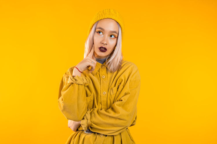 Thoughtful woman in coat against yellow background