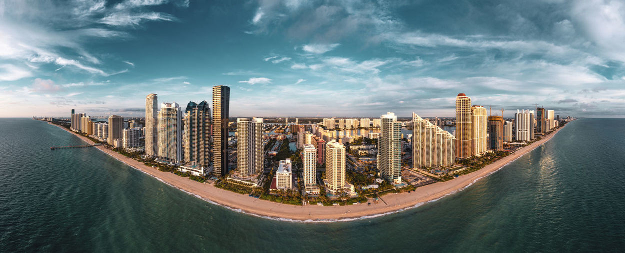 Panoramic view of modern buildings by sea against sky
