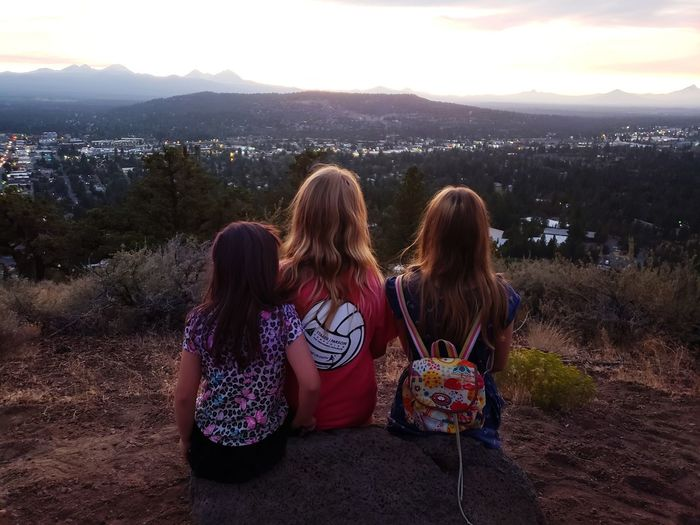 cousins View Of The Town Mountain Views Kids Girls Cousins  Friendship Young Women Togetherness Sunset Bonding Sitting Enjoyment Relaxation Long Hair Looking At View Observation Point Hiking