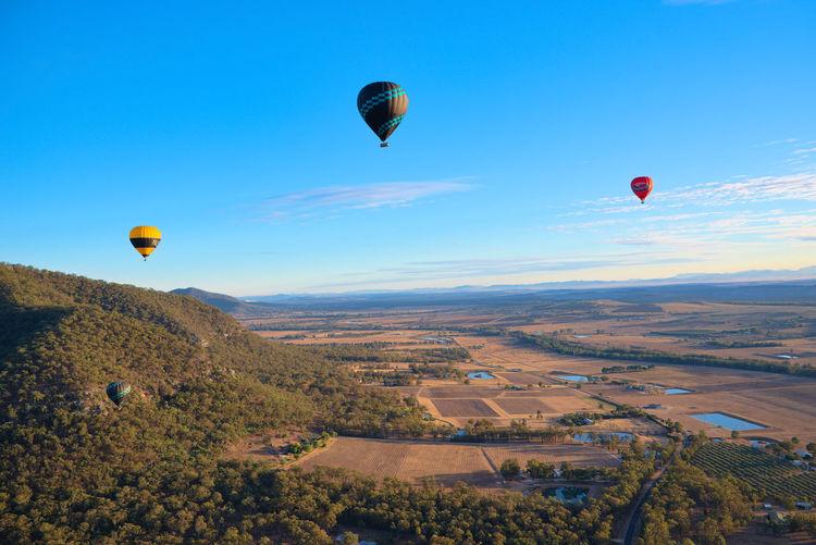 Hot air balloons flying over landscape against blue sky