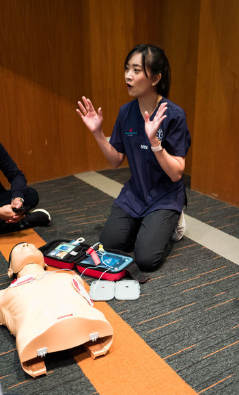 Full length of woman showing cpr over dummy on floor