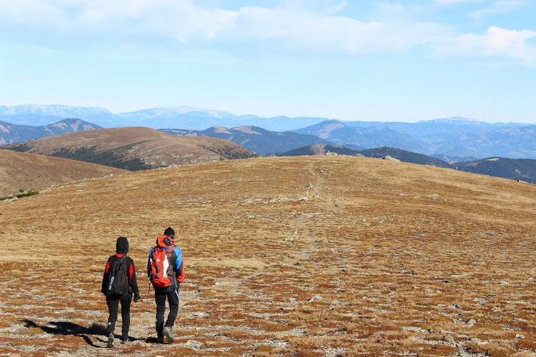 Rear view of people hiking on mountains against sky