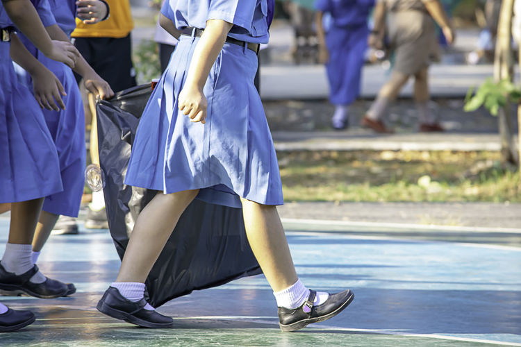 Low section of schoolgirls holding plastic bag walking outdoors