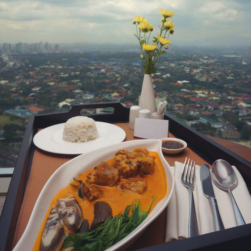 A tray of food on the edge of a table to showcase the beautiful city view from a high rise building. In photo is a classic Filipino dish called Kare-Kare composed of a peanut based sauce, fresh vegetables commonly celery and eggplant, paired with either pork or beef. Vegetables City Edge Of The World Kare Kare Lunch Rice View Bowl City Day Dining With A View Filipino Food Food Food And Drink Healthy Eating Indoors  Kare Kare Filipino Dish Meal No People Plate Pork] Room Service Raddison Blu Serving Size Sky Table