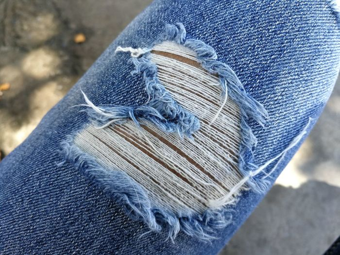 Close-up of person wearing torn jeans