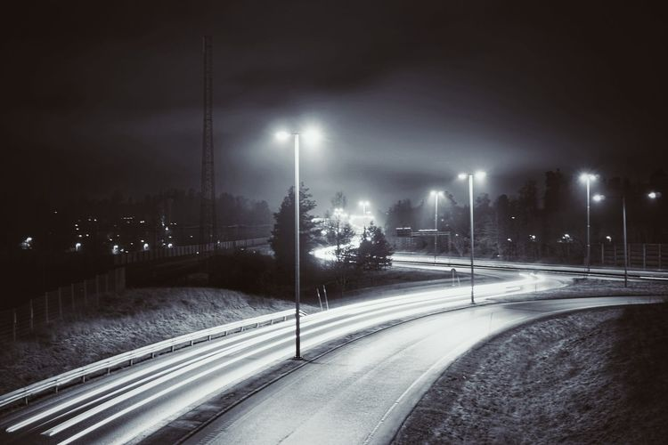 Road in city against sky at night