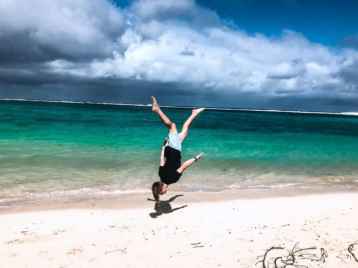 Full length of young man jumping upside down at beach against sky during sunny day