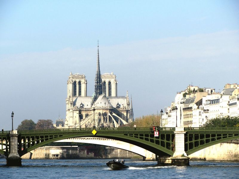 Notre-Dame de Paris (Notre Dame Cathedral) in the background with the Pont Notre-Dame bridge in the foreground crossing over the River Seine with a speedboat just in front of the bridge - Paris, France. Architecture Built Structure Building Exterior Water Waterfront Sky City River Bridge - Man Made Structure Tourism Travel Destinations Outdoors Clear Sky Connection Day 3XSPUnity Notre-Dame Notre Dame De Paris Paris Paris, France  Pont Notre Dame River Seine Seine Tourist Attraction  France