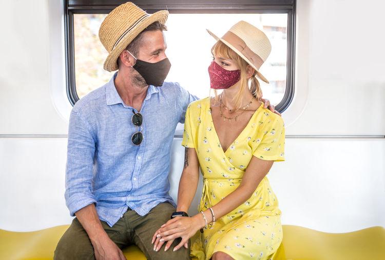Smiling couple wearing flu mask sitting in train