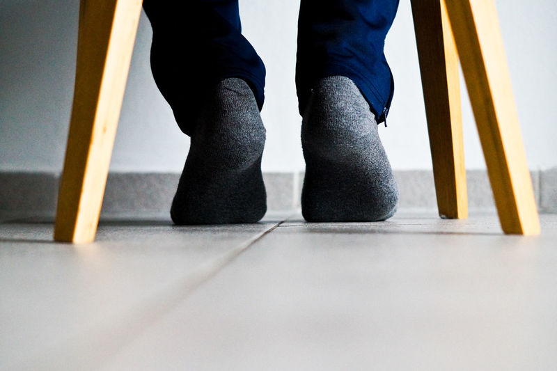 Low section of man wearing sock while sitting on table at home